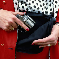 Woman carrying revolver in her purse, close-up